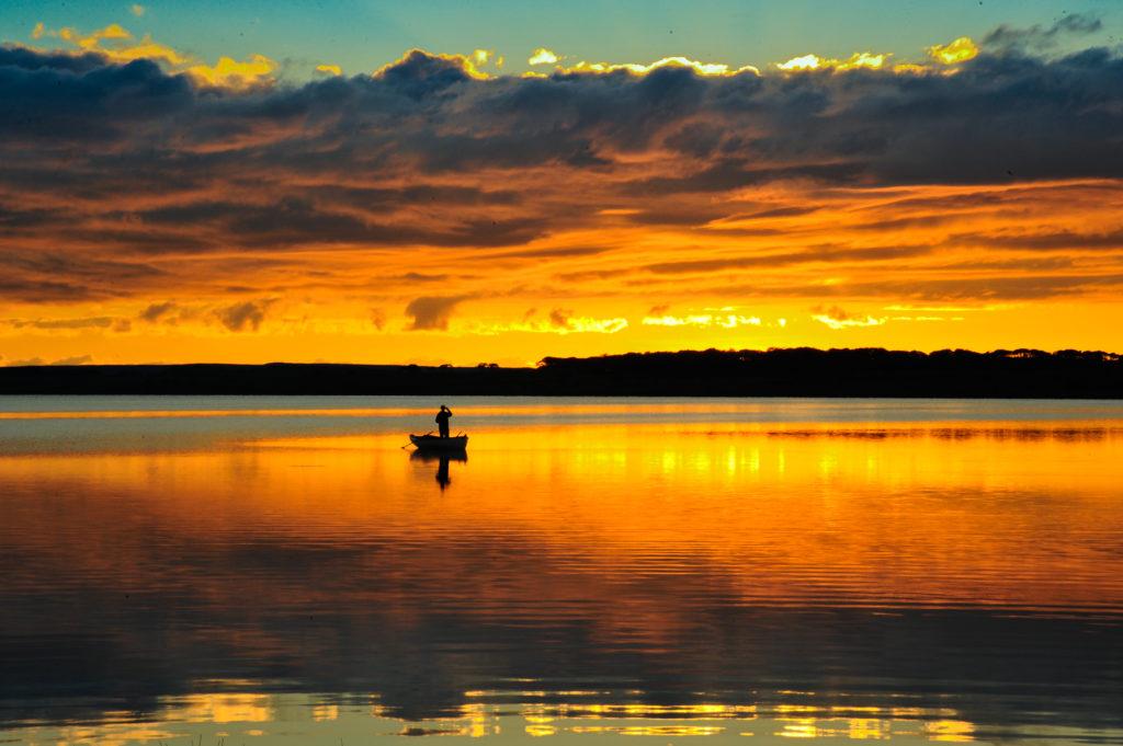 Man fishing on the lake at sunset